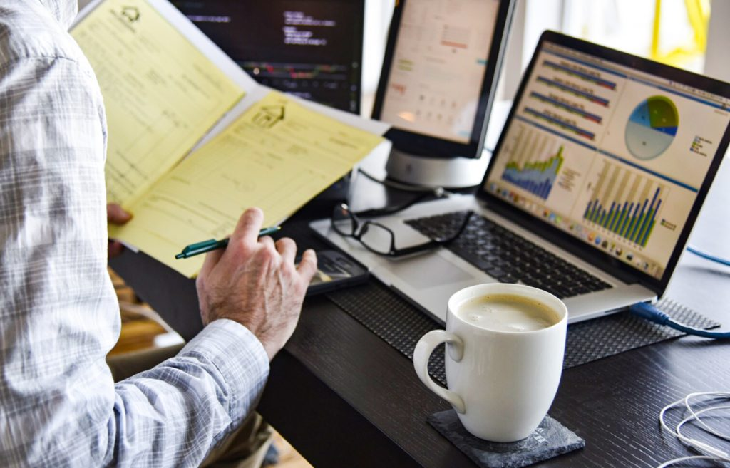 professional-at-desk-with-many-computers-signing-printed-contract-documents-coffee-charts-and-graphs_t20_NQ1Kel