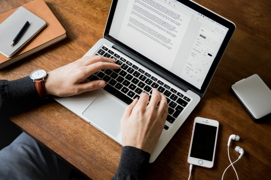 styled-lifestyle-stock-photo-of-a-man-at-a-wooden-desk-typing-on-a-laptop-computer-with-both-hands-a_t20_8ljQXW